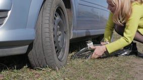 Λυπημένη γοητευτική νέα γυναίκα που ανυψώνει το σπασμένο αυτοκίνητο με τη βίδα γρύλων στον αγροτικό δρόμο κίνηση αργή φιλμ μικρού μήκους