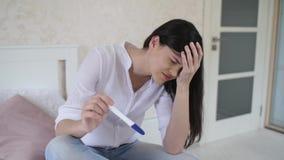 Καταθλιπτική γυναίκα με τη δοκιμή εγκυμοσύνης φιλμ μικρού μήκους