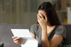 Λυπημένη γυναίκα που διαβάζει μια επιστολή στο σκοτάδι στοκ εικόνα