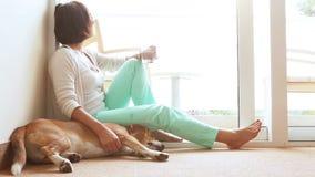 Λυπημένη γυναίκα που εγκαθιστά στο πάτωμα κοντά στο φιλικό σκυλί απόθεμα βίντεο
