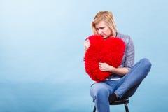 Λυπημένη γυναίκα που κρατά το κόκκινο μαξιλάρι στη μορφή καρδιών Στοκ εικόνα με δικαίωμα ελεύθερης χρήσης