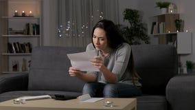 Λυπημένη γυναίκα που παραπονιέται διαβάζοντας μια επιστολή στη νύχτα φιλμ μικρού μήκους