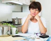 Λυπημένη γυναίκα που πληρώνει τους λογαριασμούς στοκ εικόνες