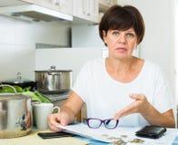Λυπημένη γυναίκα που πληρώνει τους λογαριασμούς Στοκ εικόνα με δικαίωμα ελεύθερης χρήσης