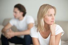 Λυπημένη γυναίκα που σκέφτεται πέρα από ένα πρόβλημα, συνεδρίαση ανδρών κατά μέρος στοκ εικόνα