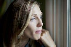 Λυπημένη γυναίκα στο παράθυρο Στοκ εικόνα με δικαίωμα ελεύθερης χρήσης