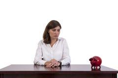 Λυπημένη επιχειρηματίας που εξετάζει τη piggy τράπεζα στοκ φωτογραφία με δικαίωμα ελεύθερης χρήσης