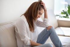 Λυπημένη καταθλιπτική γυναίκα που αισθάνεται το κακό στο σπίτι κάθισμα στον καναπέ στοκ εικόνα με δικαίωμα ελεύθερης χρήσης