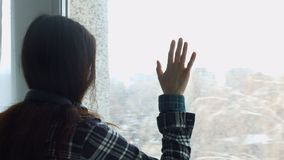 Λυπημένη καταθλιπτική νέα γυναίκα που κοιτάζει μέσω του παραθύρου απόθεμα βίντεο