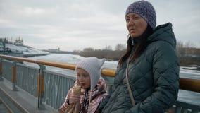 Λυπημένη κόρη που τρώει το χοτ-ντογκ ενώ στοχαστική μητέρα που περιμένει κοντά στα κιγκλιδώματα απόθεμα βίντεο