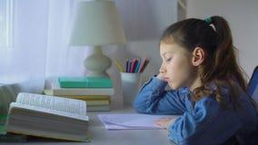 Λυπημένη μάνδρα μασήματος σχολικών κοριτσιών κάνοντας την περίπλοκη εργασία απόθεμα βίντεο