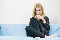 Λυπημένη μόνη συνεδρίαση γυναικών στον καναπέ με την κούπα στοκ εικόνες
