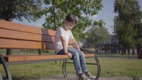 Λυπημένη μόνη συνεδρίαση μικρών παιδιών στον πάγκο στο πάρκο Χαριτωμένος χρόνος εξόδων παιδιών μόνο υπαίθρια Ελεύθερος χρόνος καλ απόθεμα βίντεο