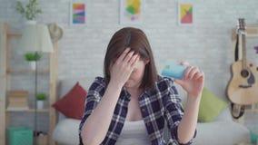 Λυπημένη νέα γυναίκα με τη διαθέσιμη συνεδρίαση χεριών πιστωτικών καρτών σε έναν πίνακα σε ένα σύγχρονο διαμέρισμα, έννοια η ιδέα απόθεμα βίντεο