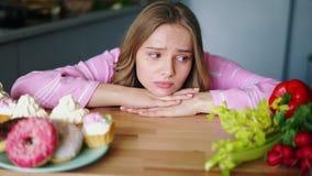 Λυπημένη νέα γυναίκα που κοιτάζει σε υγιή και το άχρηστο φαγητό διαδοχικά φιλμ μικρού μήκους