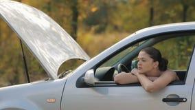 Λυπημένη νέα γυναίκα στο σπασμένο αυτοκίνητο απόθεμα βίντεο