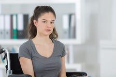Λυπημένη νέα συνεδρίαση γυναικών στην αναπηρική καρέκλα στο δωμάτιο Στοκ φωτογραφίες με δικαίωμα ελεύθερης χρήσης