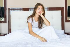 Λυπημένη νέα συνεδρίαση γυναικών στο κρεβάτι στο πρωί στοκ εικόνες
