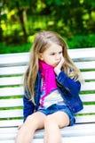 Λυπημένη ξανθή συνεδρίαση μικρών κοριτσιών σε έναν πάγκο στο πάρκο Στοκ Φωτογραφία