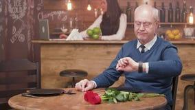 Λυπημένη παλαιά συνεδρίαση ατόμων σε έναν πίνακα σε ένα εστιατόριο και αναμονή για την ημερομηνία του απόθεμα βίντεο