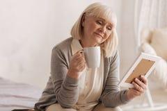 Λυπημένη στοχαστική γυναίκα που κρατά ένα φλυτζάνι του τσαγιού Στοκ Φωτογραφίες