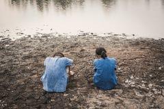 Λυπημένη συνεδρίαση αγοριών και κοριτσιών στο ραγισμένο ξηρό έδαφος Στοκ Φωτογραφίες