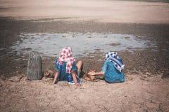 Λυπημένη συνεδρίαση αγοριών και κοριτσιών στο ραγισμένο ξηρό έδαφος Στοκ φωτογραφία με δικαίωμα ελεύθερης χρήσης