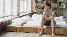Λυπημένη συνεδρίαση ατόμων στο κρεβάτι μετά από τη φιλονικία με τη σύζυγό του σχετικά με το πρόσωπό του και εξέταση το παράθυρο ε απόθεμα βίντεο