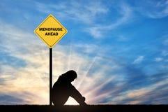 Λυπημένη συνεδρίαση γυναικών μπροστά από μια εμμηνόπαυση οδικών σημαδιών μπροστά στοκ φωτογραφίες