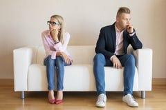 Λυπημένη συνεδρίαση ζευγών στον καναπέ και κοίταγμα στις διαφορετικές κατευθύνσεις στοκ εικόνες