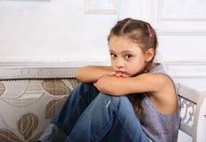Λυπημένη συνεδρίαση κοριτσιών παιδιών σκέψης και να ονειρευτεί στον πάγκο στο μπλε Στοκ Φωτογραφία