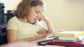 Λυπημένη συνεδρίαση κοριτσιών στον πίνακα με έναν σωρό των βιβλίων Τρίβει τα μάτια της και θέλει να κοιμηθεί Προβλήματα της σχολι απόθεμα βίντεο