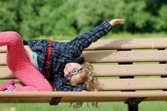 Λυπημένη συνεδρίαση μικρών κοριτσιών στον πάγκο στο πάρκο στο χρόνο ημέρας στοκ φωτογραφίες