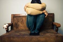 Λυπημένη συνεδρίαση ατόμων στον παλαιό καναπέ Στοκ Φωτογραφίες