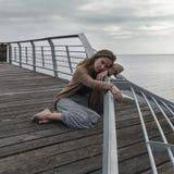 Λυπημένη συνεδρίαση κοριτσιών στο παλαιό αγκυροβόλιο Στοκ Εικόνες