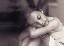 Λυπημένη συνεδρίαση μικρών κοριτσιών στη στρωματοειδή φλέβα παραθύρων και να φανεί έξω το W στοκ φωτογραφία με δικαίωμα ελεύθερης χρήσης