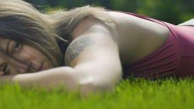 Λυπημένη συντετρημμένη γυναίκα που βρίσκεται στη χλόη που κοιτάζει επίμονα, τέλος των σχέσεων, θλίψη φιλμ μικρού μήκους