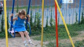 Λυπημένη ταλάντευση κοριτσιών παιδιών στην παιδική χαρά απόθεμα βίντεο