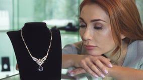 Λυπημένη τοποθέτηση γυναικών με ένα ακριβό περιδέραιο διαμαντιών στο κατάστημα απόθεμα βίντεο