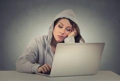 Λυπημένη τρυπημένη νέα γυναίκα που χρησιμοποιεί τη συνεδρίαση lap-top στον πίνακα Στοκ φωτογραφία με δικαίωμα ελεύθερης χρήσης