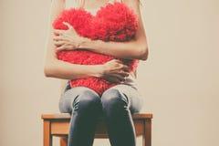 Λυπημένη δυστυχισμένη γυναίκα που κρατά το κόκκινο μαξιλάρι καρδιών Στοκ φωτογραφία με δικαίωμα ελεύθερης χρήσης