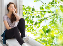Λυπημένη όμορφη συνεδρίαση έφηβη στο windowsill Στοκ Φωτογραφίες