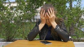 Λυπημένη όμορφη συνεδρίαση κοριτσιών σε έναν πίνακα σε έναν καφέ Διαβάζει sms σε ένα smartphone Έχει τα αγκαλιάσματα το κεφάλι το απόθεμα βίντεο