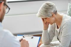 Λυπημένοι ανώτεροι ασθενής και ψυχολόγος γυναικών στοκ εικόνα