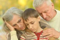 Λυπημένοι παππούδες και γιαγιάδες με το αγόρι στο πάρκο Στοκ Φωτογραφία