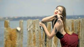 Λυπημένος ένας ξανθός με μακρυμάλλη σε ένα κόκκινο φόρεμα κρατά επάνω στις ξύλινες θέσεις κάτω από τα μπουρίνια του αέρα, στη μέσ απόθεμα βίντεο