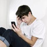 Λυπημένος έφηβος με το κινητό τηλέφωνο Στοκ εικόνες με δικαίωμα ελεύθερης χρήσης