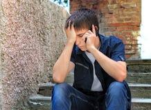 Λυπημένος έφηβος με το κινητό τηλέφωνο Στοκ Εικόνες