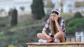 Λυπημένος έφηβος που ακούει τη μουσική στις διακοπές απόθεμα βίντεο