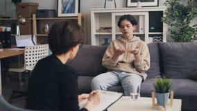 Λυπημένος έφηβος που ανοίγει στον επαγγελματικό θεράποντα στο γραφείο του ψυχολόγου απόθεμα βίντεο